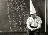 "Boy in dunce cap. Repeated writing on the chalkboard behind him reads ""I will be Good."""