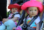 Two girls sitting in a double-stroller, wearing bright sun hats.