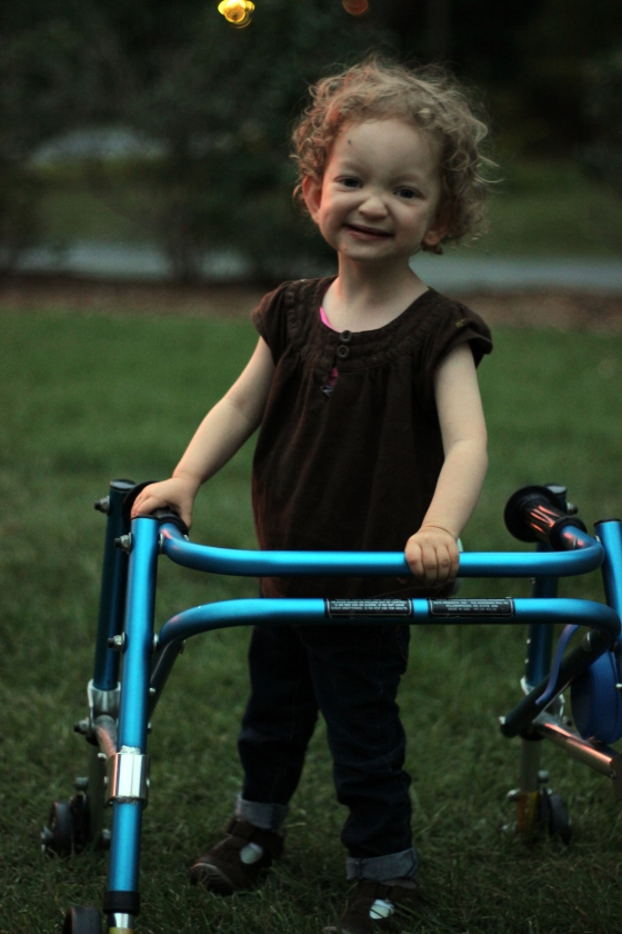 Fiona smiling with her blue metallic walker, on a summer-green lawn at sunset.