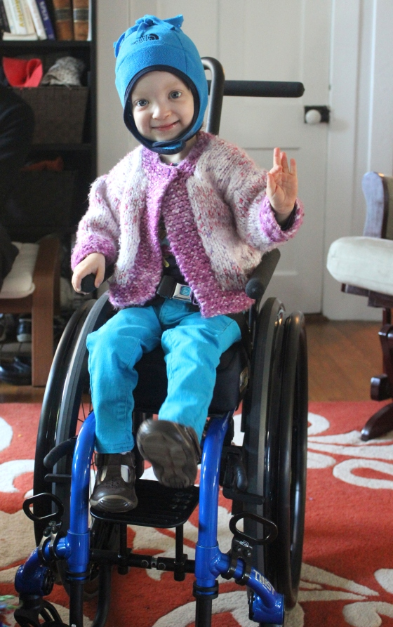 Fiona smiling in her wheelchair, holding her left hand in a mudra.