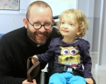 Fiona sitting in her wheelchair at preschool, my husband squatting and smiling beside her.