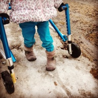 Fiona from waist to boots, pushing two walker wheels over snow.