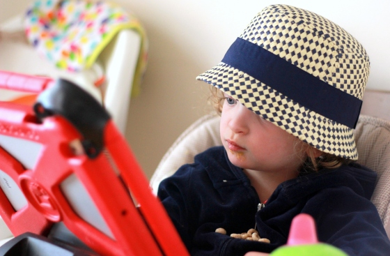 Side-angle of Fiona in a blue and cream straw hat, looking at her talker--an iPad encased in a red foam frame.