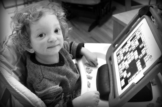 Black & white of Fiona, sitting at a highchair, looking at the camera. Her talker is on a tray in front of her.