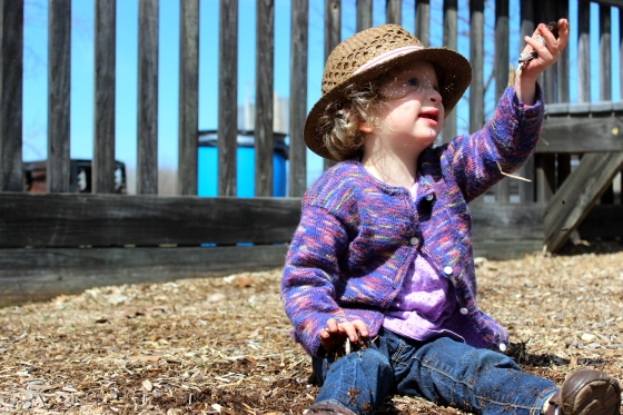 {Image description: Fiona is seated on the ground, wearing a straw hat and purple cardigan sweater, lifting a handful of wood chips above her head, looking up at it and smiling. FYI: She freaking loves wood chips}