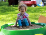 [Image description: Fiona in a green outdoor sandbox, smiling, looking straight into the camera.]