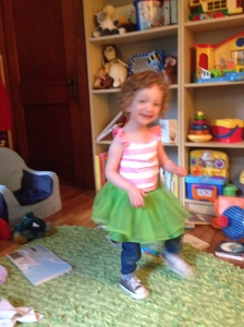 [Image description: Fiona blurring by in a striped tank top, green tutu, and jeans.]