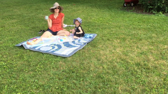 [Image Description: Fiona and I, sitting on a blanket on the lawn, both looking straight at the camera. I'm holding a cup of tea. Fiona is smiling. We're both wearing sun hats.]