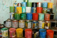 [Image Description: Stacked rows and columns of spilling paint cans.]