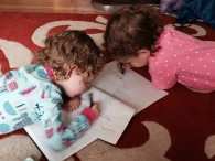 [Image description: Petra and Fiona, lying on their bellies in their PJ's, drawing with black pens in a lined notebook.]