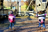 [Image: The backs of Fiona and Petra, who are in the swings.]