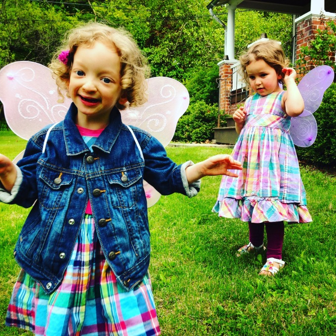Fiona is in the foreground, looking at the camera, and her 3-year-old sister is in the background, looking at her Fee. They're on green grass, wearing pastel plaid dresses. They both have glittery butterfly wings on their backs.