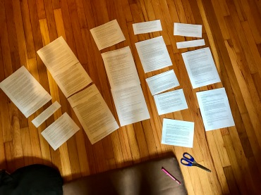 {Image: Several chunks of typed text cut up and arranged in five columns, spread out on a wood floor. A pink pen and a pair of scissors is at the bottom right of the photo.}