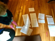 {Image: the same as before--typed chunks of text on pages, spread out on a wood floor, only Fiona is standing beside them in a navy sweatshirt and pink pants.}