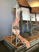 Image: part of a Hite sculpture. Rickety stairs made of beach-pink wood, interrupted in the middle by a four-rung ladder. The stairs are leading up to a white building only partly shown, held up by the stilts of driftwood.